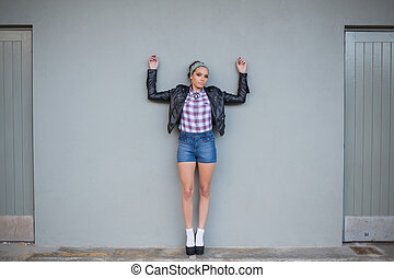 Sexy woman posing on a grey wall
