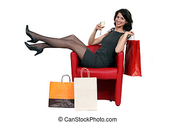Sexy woman posing with her shopping bags and drinking a...