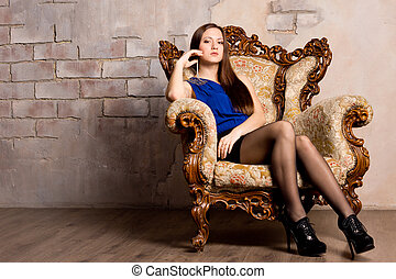 Sexy woman reclining in an armchair