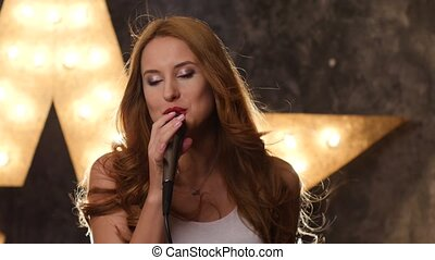 sexy woman singer with red lips and microphone, shining star in the background. close up