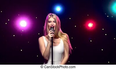 Sexy woman singing into a retro microphone. Slow motion