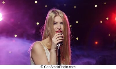 Sexy woman singing into retro microphone strobe lighting and smoke effect