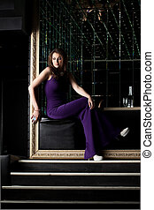 Sexy woman sitting in purple long dress