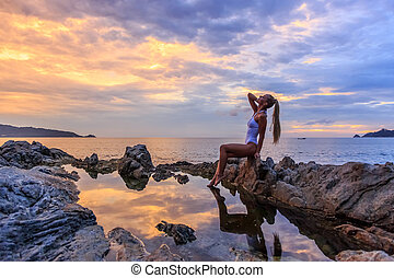 Sexy woman sitting on the rocks at sunset