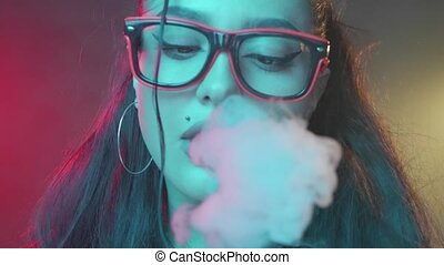Sexy woman smoking in neon color light - Gorgeous brunette...