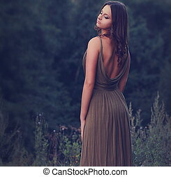 Sexy woman standing in dress with nude back on nature background