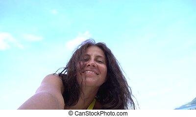 Sexy woman taking selfie using phone on beach smiling, enjoying vacation