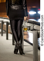 woman wearing high heels holding whiskey bottle