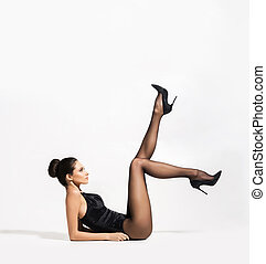 Sexy woman wearing stockings and heels with hot legs up in...