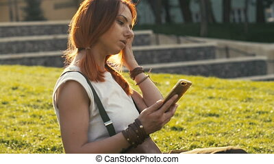 Sexy woman with red hair holding and mobile phone on summer...