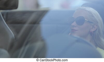 Sexy woman with red lipstick sitting behind the wheel of the cabriolet