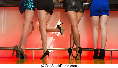 Sexy women legs standing back to camera and posing at bar in...