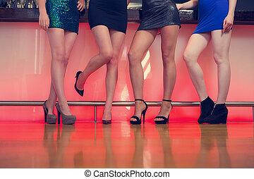 Sexy women legs posing at a bar in a nightclub