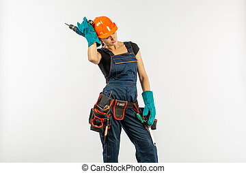 sexy workwoman in overalls and safety helmet with tool belt...