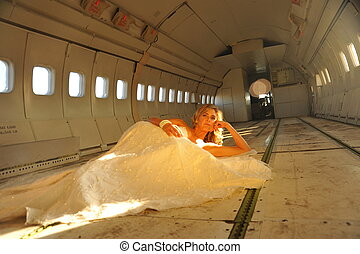 sexy young adult bride model in white laying in the fuselage of airplance