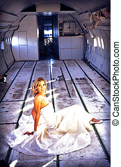 sexy young adult bride model in white sitting in the fuselage of airplane