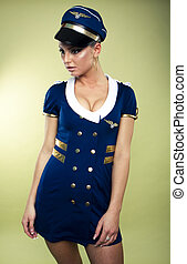 Sexy young air stewardess wearing hat in mini skirt, studio...