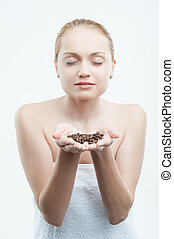 Sexy young attractive woman with coffee beans in hands