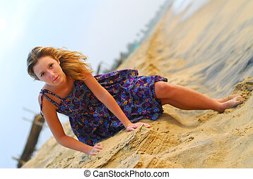 Sexy young blond girl sitting on beach