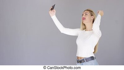 Sexy young blond woman posing for a selfie