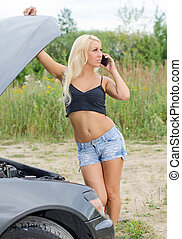Sexy young blond woman with cellphone near broken car.