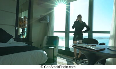 Sexy young blonde business woman is talking on the phone in the hotel room or office, concluded a deal. Business trip. Beautiful lady speaks by mobile and looking at sea, sky