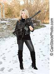 Sexy young blonde with a gun