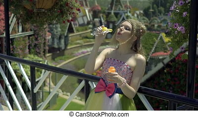Sexy young blonde woman blowing soap bubbles in flower garden. Pretty dreaming cute girl in funny lace dress relaxes, enjoys, have fun, falling in love, among the flowers. Happy face. Slow motion