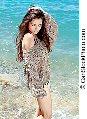 Sexy young brunette female on beach, outdoors portrait....