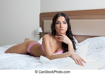 Sexy young brunette woman lying on bed
