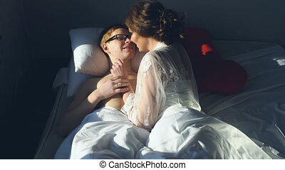 Sexy young couple kissing and playing in bed on their marriage day