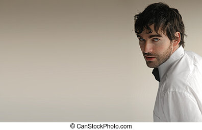 Sexy young elegant man turning toward camera against off white background and lots of copy space
