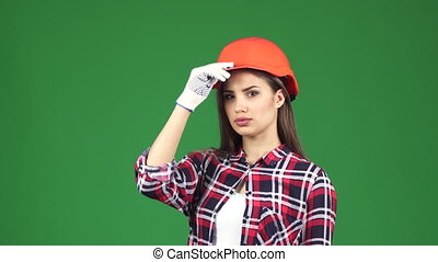 Sexy young female contractor wearing hardhat showing thumbs...