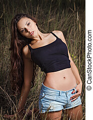 Sexy young girl in a field at evening time