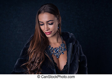 Sexy young girl in an expensive fur coat with luxurious blue jewelry