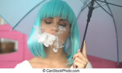 Sexy young girl in modern futuristic style with blue wig smoking e-cigarette