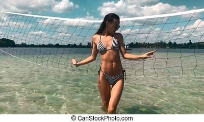 sexy young girl posing at the volleyball nets in the sea in...