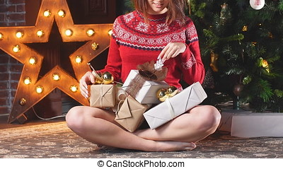 Sexy young girl sitting by Christmas tree with gifts.