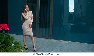 girl with long hair on the heels and trendy attire stands on the street and said by mobile phone