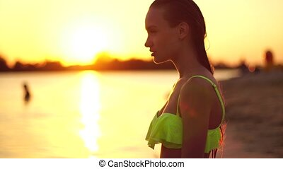 Sexy young lady in swimsuit at sunset at the warm evening