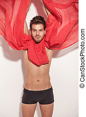 Sexy young man fluttering a red scarf