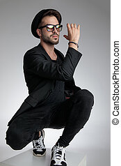 sexy young man holding elbow in a fashion pose