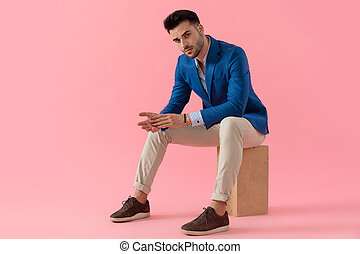 sexy young man holding elbows on knees in a fashion pose