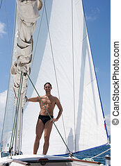 Sexy young man sailing on white yacht