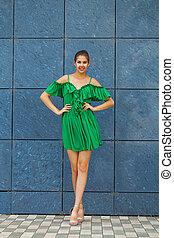 Full body portrait young beautiful brunette woman in green dress