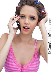 Sexy young model wearing hair rollers with phone
