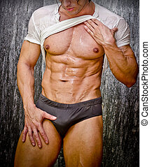 Sexy young muscular man in shower wearing underwear and wet t-shirt