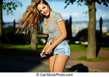 sexy young stylish smiling woman girl model in bright modern cloth with perfect sunbathed body outdoors in the park in jeans shorts with flying elevated hair in air