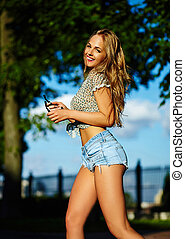 sexy young stylish smiling woman girl model in bright modern cloth with perfect sunbathed body outdoors in the park in jeans shorts running