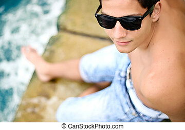sexy young trendy man in sunglasses on the beach. Focus on...
